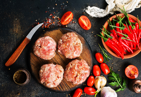 raw cutlets for burger on wooden board