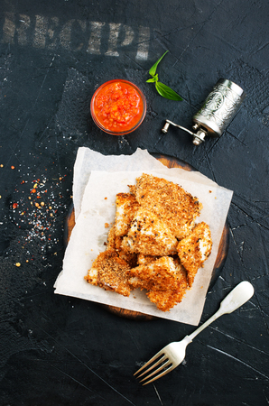 Pan fried fish with tomato sauce on a table Фото со стока - 104299072