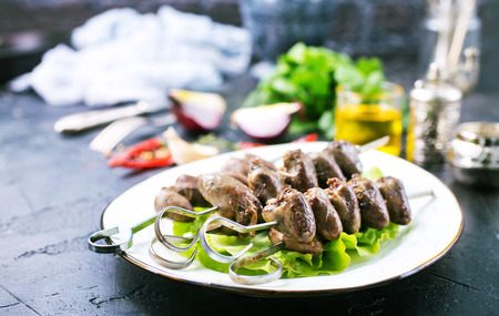 Fried hearts with spice. Chicken hearts kebab with salad on a plate top view 版權商用圖片