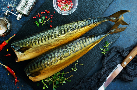 smoked fish, fish with red pepper, fish on the board Фото со стока