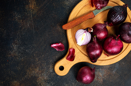 raw onions on wooden board, stock photo