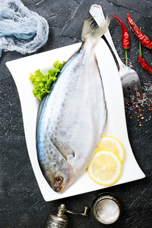 raw fish with fresh lemon on plate Stock Photo