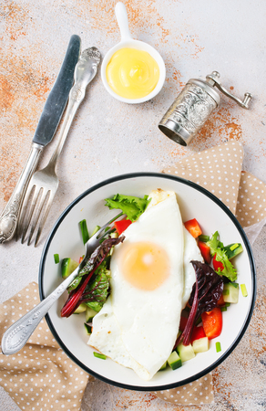 breakfast on plate, fried egg with salad