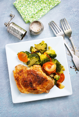 Fried meat with vegetables on white plate