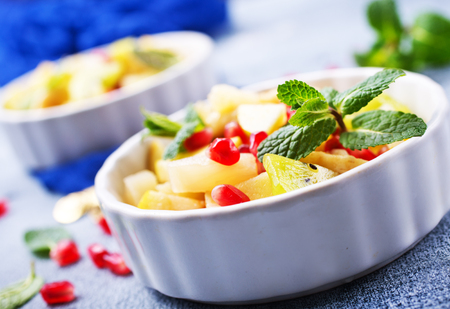 Fruit salad in bowl, vitamin salad with mint leaf