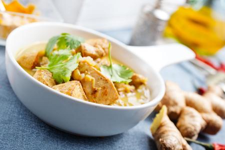 Curry de poulet dans un bol blanc sur une table