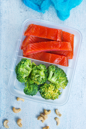 Red fish with boiled broccoli, diet food in lunchbox