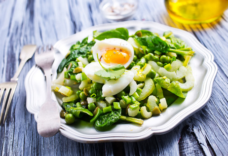 Salad with boiled egg and fresh spinach on plate