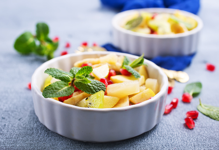 Fruit salad in bowl, vitamin salad with mint leaf