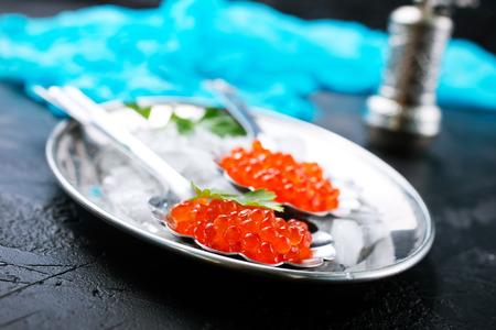 red salmon caviar in metal spoon on metal tray Stock Photo