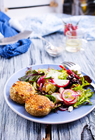chicken cutlets and greeck salad on plate Imagens