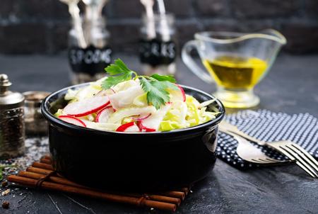 salad from fresh cabbage and radish, salad in black bowl 版權商用圖片