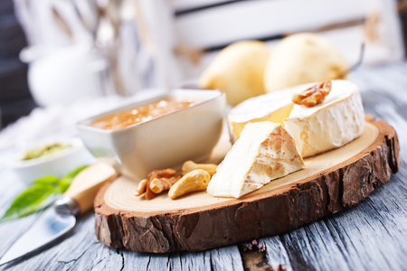 cheese nuts honey and fresh pears on wooden board Stock Photo