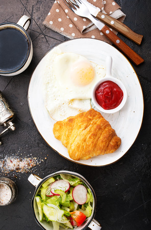 breakfast on a table, fried eggs and croissant