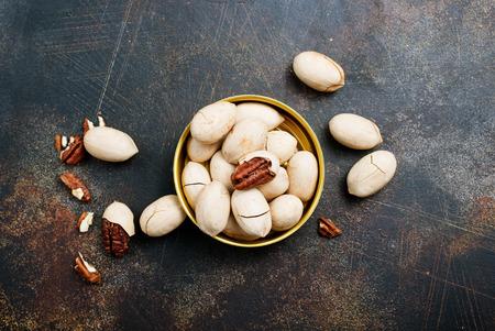 Pecan nuts in metal bowl, pecan nuts in shell Фото со стока