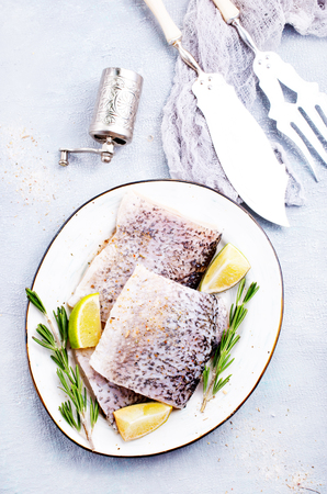 Fresh fish, raw cod fillets with rosemary and salt Stock Photo