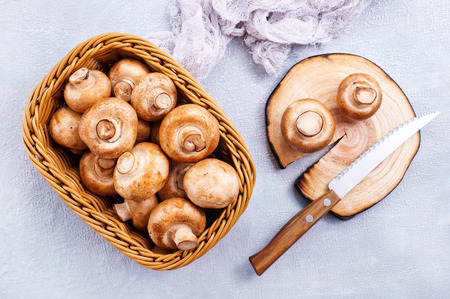 basket of champignon mushrooms on old  table