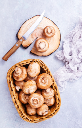 basket of champignon mushrooms on old  table