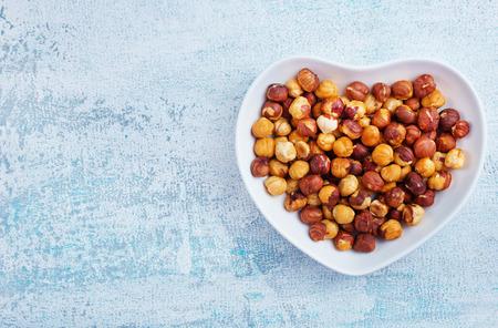 hazel nuts in white bowl, dry hazelnuts Imagens - 118683437