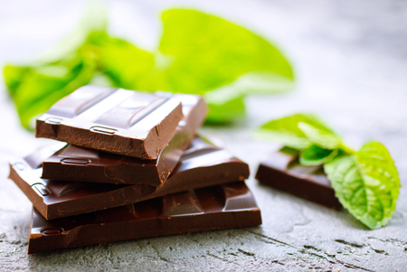 chocolate and mint leaf on a table Banco de Imagens