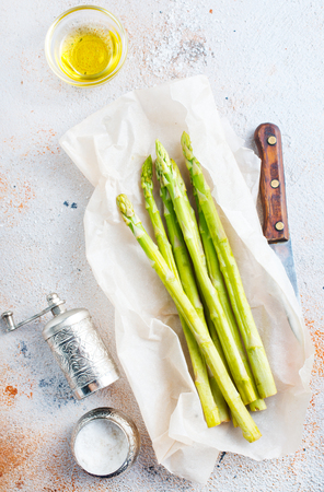 green asparagus on paper on a table