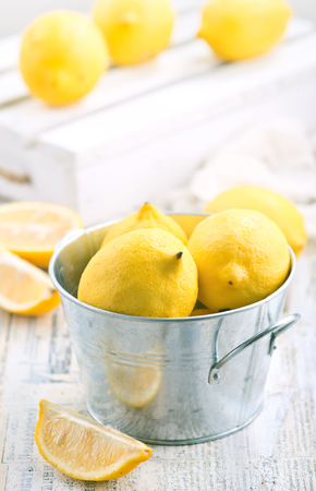 fresh lemons in metal bowl and on a table