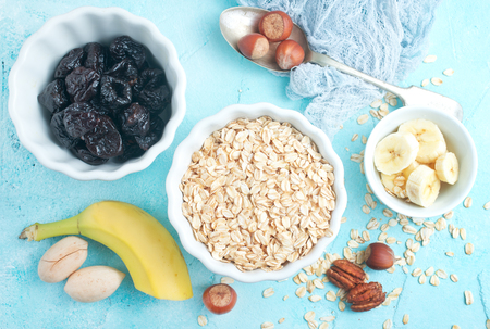ingredients for helthy breakfast, raw oat flakes with banana and nuts