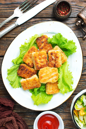 fish nuggets with latuk salad on plate, fried nuggets