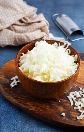 Grated cheese on wooden cutting board. cheese in bowl