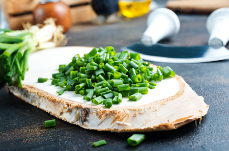 green onion, fresh  onion and knife on kitchen table Banco de Imagens - 123144440