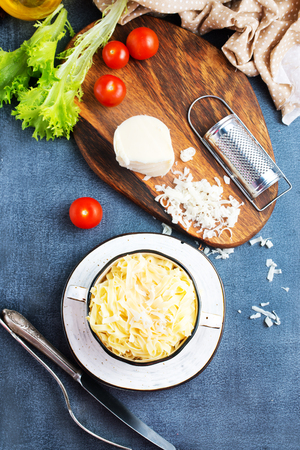 boiled noodles with grated cheese in bowl