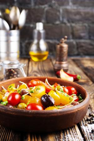 Tomatensalat mit Öl und Oliven in Schüssel Standard-Bild
