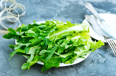 fresh rucola on plate and on a table