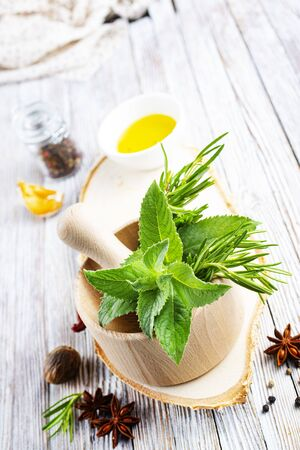 Herbs. Fresh green organic aromatic herb leaves in wooden mortar