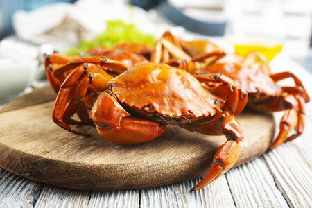 Cooked crab on wooden board/ Seafood boiled red stone crab with spices