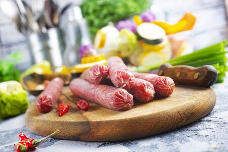 raw sausages with aroma spice on wooden board Stockfoto
