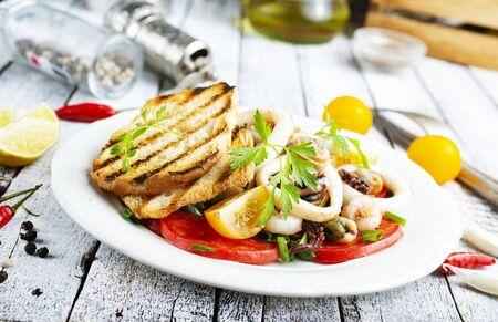 Ensalada con verduras frescas picatostes de mariscos en la placa