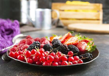 Fresh organic summer berries mix in round plate