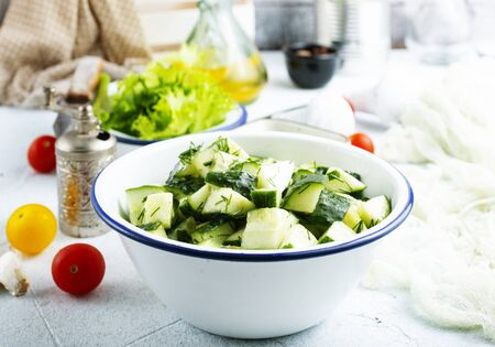 Cucumber salad in meta bowl. Salad with cucumbers and tomato.