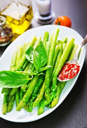 green asparagus, fresh asparagus on plate and on a table Imagens