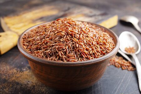 Brown rice, raw rice in bowl on a table Stock Photo