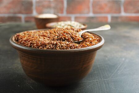 Brown rice, raw rice in bowl on a table