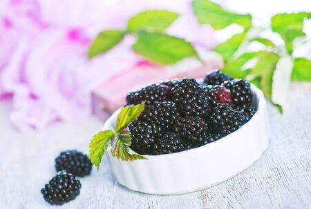 blackberry in bowl and on a table
