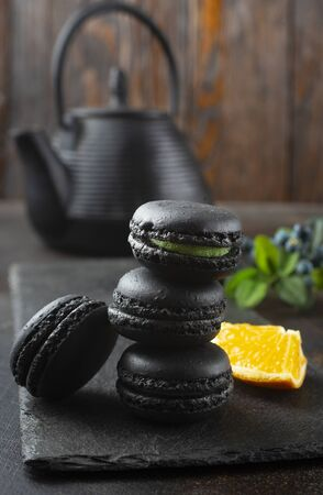 Macaroon cakes on black board. Delicious dessert.