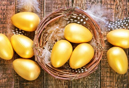 golden eggs in nest and on a table