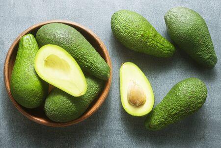 fresh avocado in brown bowl, green avocado Фото со стока