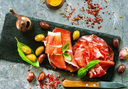 Smoked Parma ham on the black board Standard-Bild