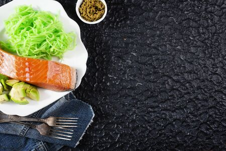 Raw Salmon with Avocado on plate, diet food