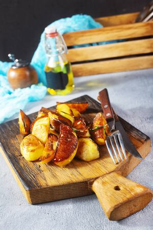 fry potatoes on wooden board. fry potatoes with fork and knife.