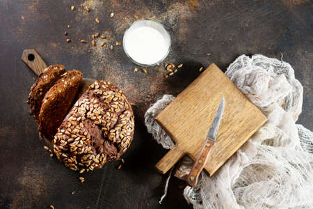 Homemade rustic rye bread with sunflower seeds and a bottle of milk on old table